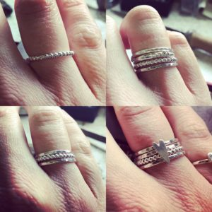 A selection of sterling silver stacking rings by chloe michell. image shows new dot ring, band with small silver heart , beaten silver band and a granulated band